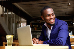 Smiling black businessman with laptop at cafe