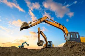 Three excavators work on construction site at sunset